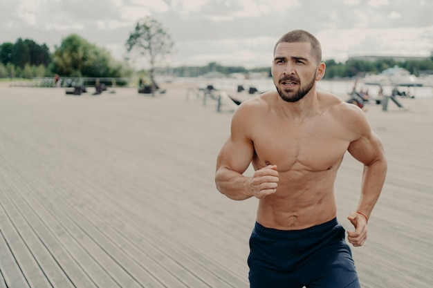 Colpo all'aperto dell'uomo caucasico muscolare senza camicia motivato si prepara per correre la maratona, va regolarmente a fare jogging la mattina presto, concentrato da qualche parte nella distanza.