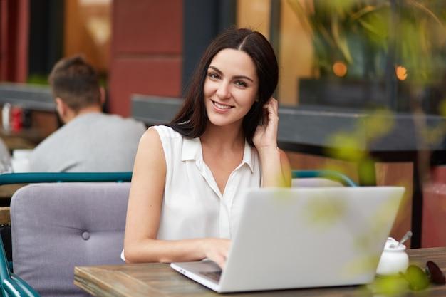 Scatto all'aperto di una giovane donna bruna dall'aspetto piacevole con un sorriso affascinante, trascorre il tempo libero nell'accogliente ristorante, lavora al computer portatile, cerca in internet e messaggi con gli amici, usa la connessione wi fi