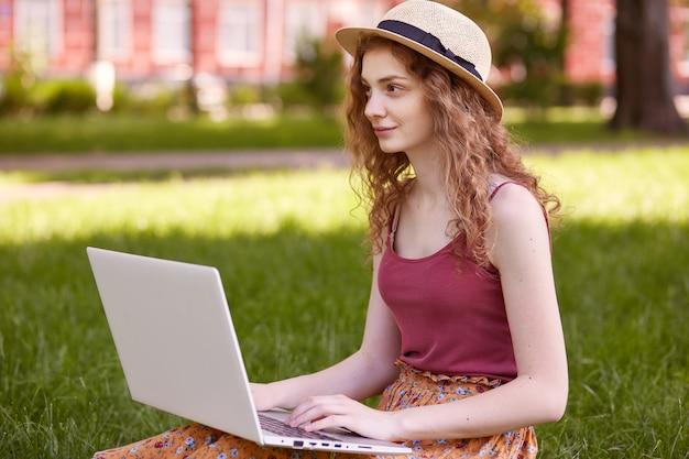 Colpo all'aperto della giovane donna graziosa che si siede nel parco con il computer portatile sulle gambe, trascorrendo la giornata estiva lavorando all'aperto, guardando a distanza, indossando maglietta, gonna e cappello, ragazza ama il lavoro online all'aria aperta.