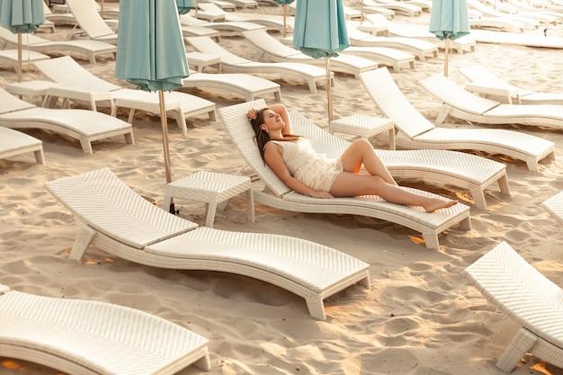 Colpo all'aperto di una donna sexy che si gode il riposo sul lettino in spiaggia