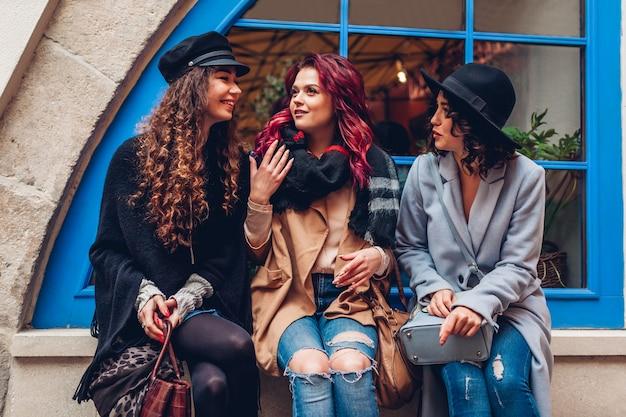 Colpo all'aperto di tre giovani donne che chiacchierano e ridono sulla strada della città. migliori amici che parlano e si divertono al caffè. ragazze felici