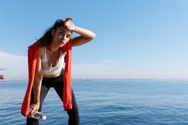 Colpo all'aperto di giovane sportiva stanca che ha una pausa vicino al mare, asciugandosi il sudore e ansimando dopo la corsa.