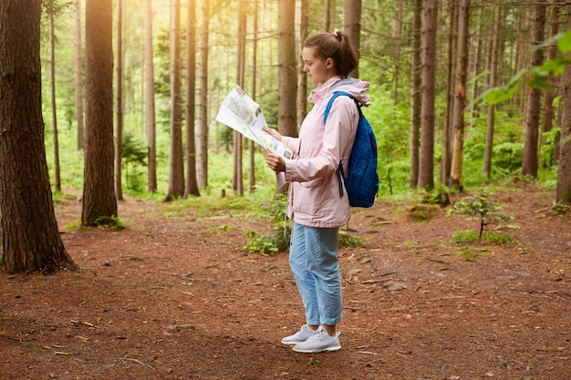 Colpo all'aperto di giovane femmina caucasica che indossa jacke e pantaloni rosa, con gli zainhi e la mappa blu, signora attraente che è in legno