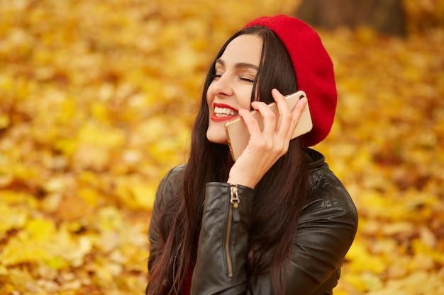 Colpo all'aperto di giovane donna dai capelli scura caucasica felice con lo smartphone, affascinante signora seduta sul terreno circondato di foglie gialle, indossa giacca di pelle e berretto rosso.