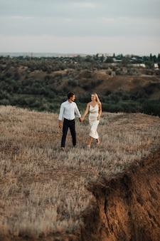 Colpo all'aperto di una giovane coppia di sposi camminando sulla collina e tenendosi per mano.
