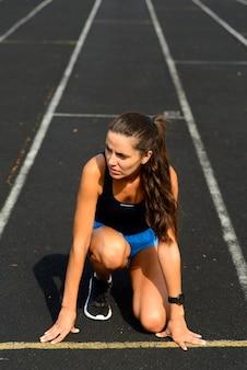 Colpo all'aperto dell'atleta della giovane donna che corre sulla pista. sportiva professionista durante la sessione di allenamento in esecuzione.