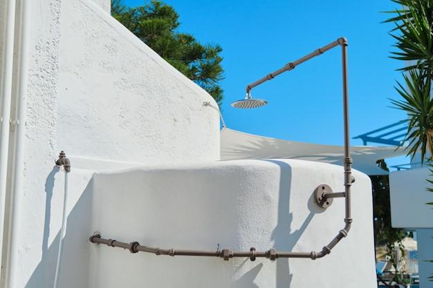 Doccia esterna, doccia in pietra bianca, cielo azzurro.