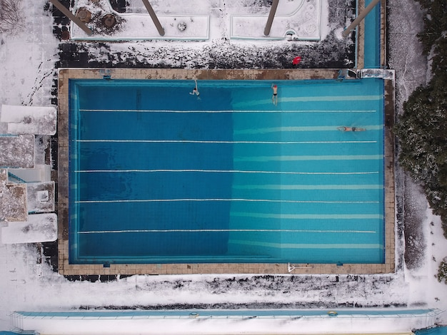 Piscina sportiva all'aperto aperta tutto l'anno. gli atleti nuotano in piscina in inverno. vista dal drone.