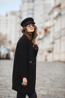 Ritratto di primavera all'aperto di giovane donna alla moda elegante che indossa occhiali da sole alla moda, cappotto rosso e cappello che cammina in una strada della città europea.