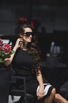 Ritratto estivo all'aperto di una donna modello che indossa occhiali da sole alla moda e abiti alla moda seduti al tavolino del bar nella strada di una città europea