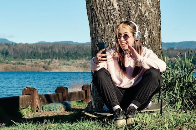 Ritratto di estate all'aperto di riposo giovane donna con longboarding mandare sms alla sua amica.