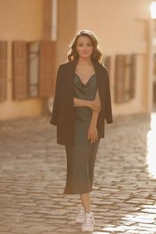 Ritratto estivo all'aperto di una giovane donna che indossa un abito alla moda e giacca che cammina alla luce del sole per la strada di una città europea