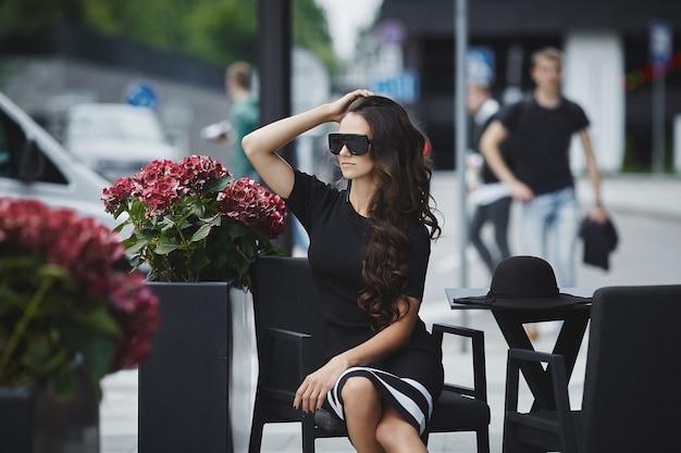 Ritratto estivo all'aperto di una giovane donna che indossa occhiali da sole alla moda e abiti alla moda seduti al tavolino del bar nella strada di una città europea