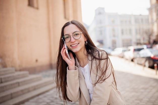Videoconferenza all'aperto ritratto di una bella donna giovane donna parla al telefono in piedi sulla strada nel centro della città