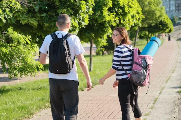 Uomo e donna a piedi all'aperto in abbigliamento sportivo con zaini