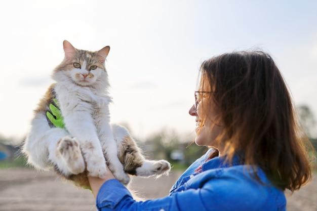 Donna all'aperto che tiene in braccio un gatto domestico e parla con lei, amicizia del proprietario e dell'animale domestico