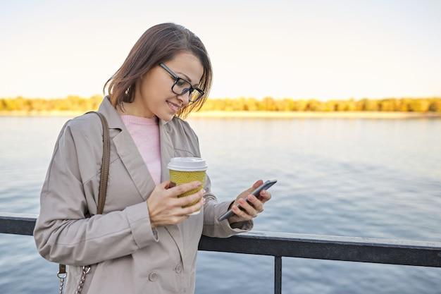 Ritratto all'aperto della donna, femmina sorridente con la tazza di caffè e lo smartphone