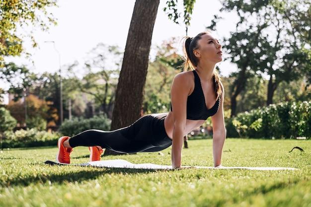 Concetto di allenamento all'aperto. una giovane donna in tuta esegue esercizi per allungare i muscoli del corpo, prasana dallo yoga.