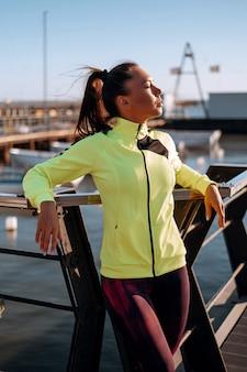 Concetto di allenamento all'aperto. giovane donna in tuta esegue allenamento sportivo sul molo