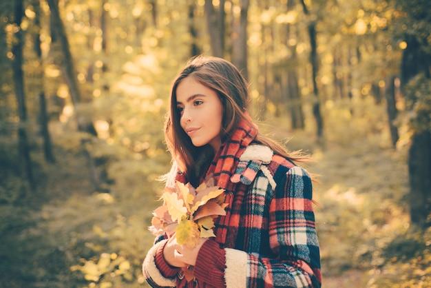 Ritratto di moda stile di vita all'aperto di bella giovane donna che cammina sul parco in autunno. foto di moda atmosferica all'aperto di giovane bella signora nel paesaggio autunnale