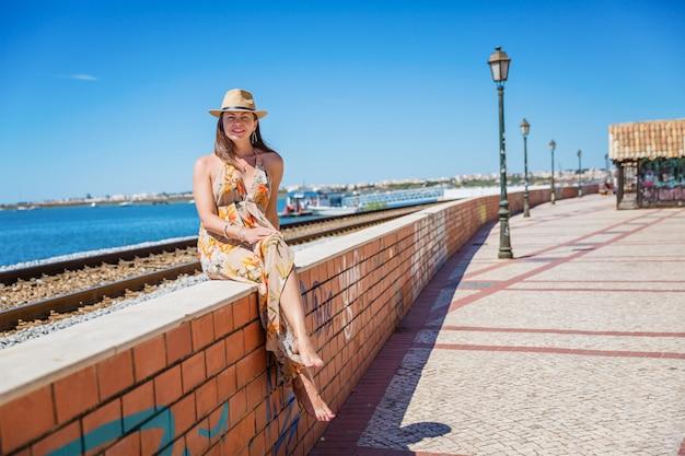 All'aperto lifestyle moda ritratto splendida donna seduta sul marciapiede. sfondo ferroviario. indossa un elegante abito lungo, bracciali e cappello di paglia.