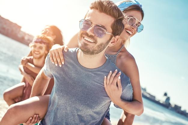 Foto all'aperto di fidanzati felici che trasportano sulle spalle le loro amiche al tramonto sulla spiaggia