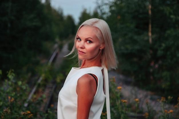 All'aperto ritratto donna adulta sulla natura che cammina nella foresta estiva del crepuscolo. la signora sognatrice vestita cammina la sera nel parco. emozione positiva della donna nel parco all'alba