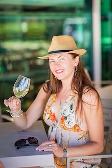Ritratto all'aperto di un'attraente donna turistica con cappello di paglia che assaggia e beve vino bianco in un bar o ristorante di strada