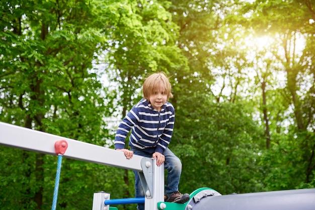 Ritratto all'aperto del ragazzo prescolare sveglio che scala al campo da giuoco