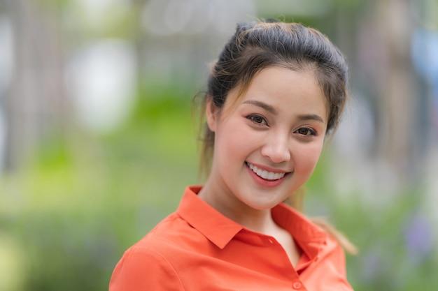 Ritratto all'aperto di giovane donna felice con la faccia sorridente