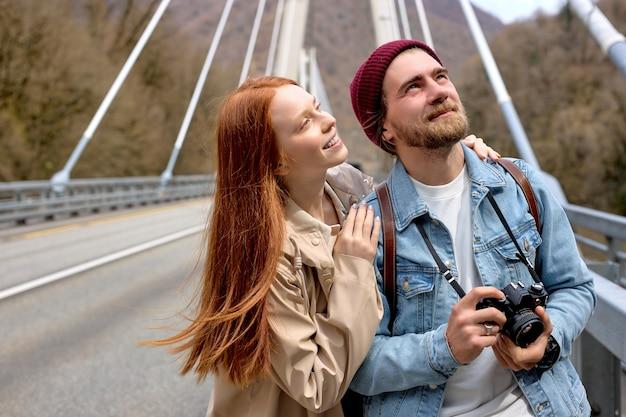 Ritratto all'aperto di uomo e donna in abiti casual e caldi che fanno una passeggiata sul ponte