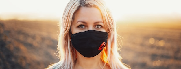 Ritratto all'aperto di donna che indossa maschera respiratoria contro il coronavirus e il covid-19.