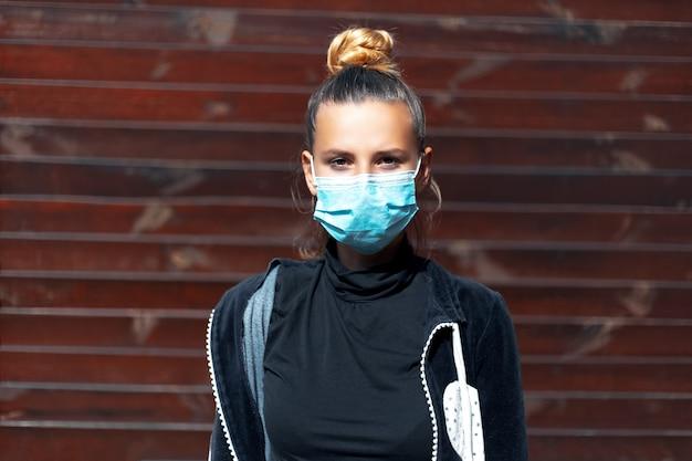 Ritratto all'aperto di giovane ragazza che indossa maschera antinfluenzale medica sul viso contro il coronavirus