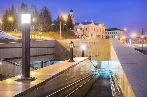 L'atrio esterno della metropolitana del cremlino a kazan e il tempio del monastero di giovanni battista alla luce delle luci notturne. didascalia: metropolitana del cremlino. stazione del cremlino