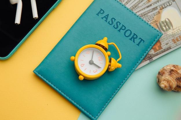 Vestito e accessori del viaggiatore sul primo piano di superficie blu giallo. concetto di viaggio. vista dall'alto degli accessori del viaggiatore