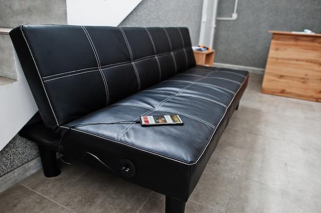 Presa e caricatore usb integrati in un divano in pelle nera per caricare il telefono cellulare.