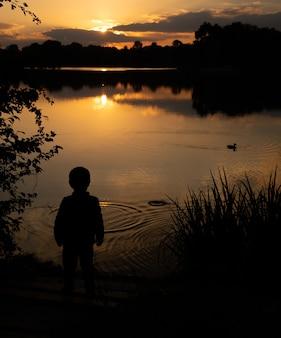 Profilo di un ragazzo al tramonto sul lago