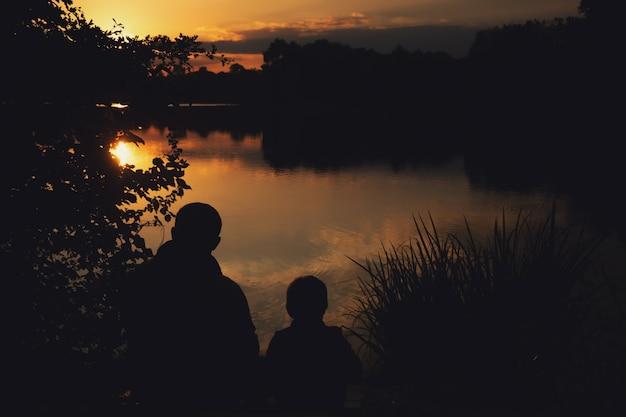 Profilo di un ragazzo con papà al tramonto sul lago