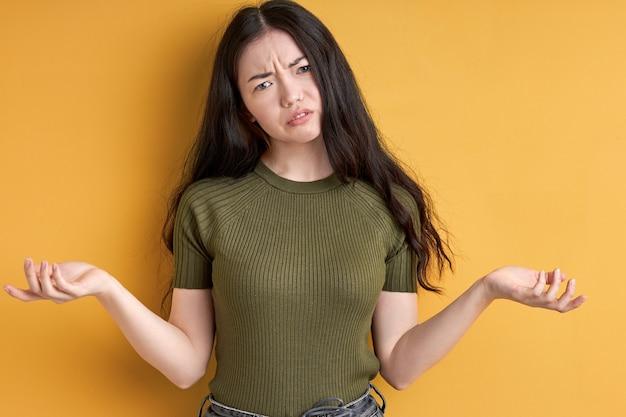 Indignata donna caucasica con capelli lunghi neri alzando la mano ed esprimendo incomprensioni isolate su sfondo giallo