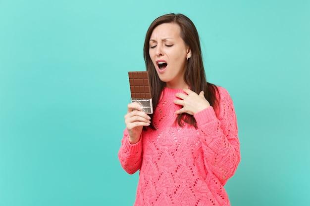 Indignata giovane donna irritata in maglione rosa lavorato a maglia tenere in mano, guardando la barretta di cioccolato isolata su sfondo blu turchese parete, ritratto in studio. concetto di stile di vita della gente. mock up copia spazio.