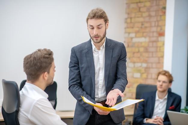 Gestore giovane adulto indignato con documenti in mano che chiedono chiarimenti dal dipendente seduto accanto a lui