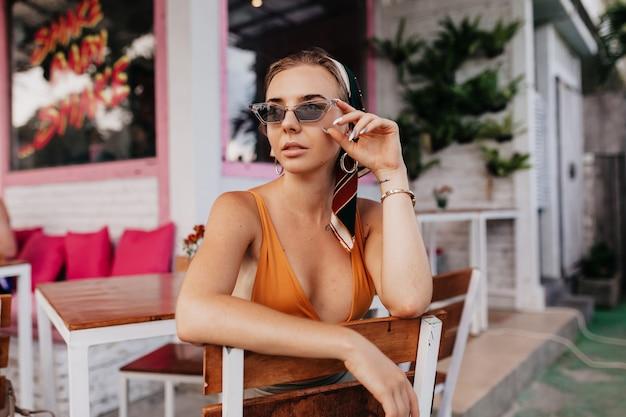 Ritratto esterno di bella donna in occhiali da sole che riposa fuori ritratto esterno di donna elegante che beve il tè in un ristorante sulla strada