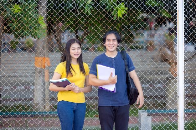 Al di fuori della scuola, una giovane coppia di studenti felice sta in piedi lungo una staccionata, studiando un libro.