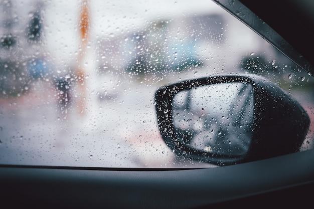 Vista dall'esterno la pioggia caduta fa goccioline d'acqua attraverso l'auto e lo specchietto retrovisore.