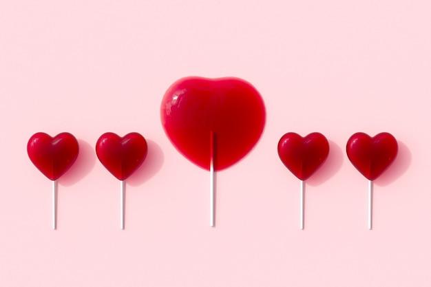 Eccezionale melt a forma di cuore rosso di caramelle lecca-lecca su sfondo rosa. rendering 3d. idea minima del concetto di san valentino.