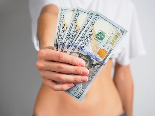 Nella mano femminile tesa, banconote da 100 dollari. la donna porge i soldi. il concetto di ricchezza, solvibilità. sfondo sfocato. concentrarsi sulle banconote