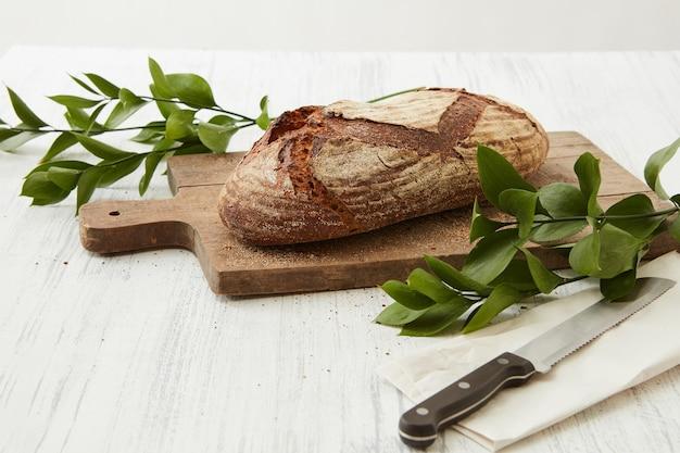 Pane ovale appena sfornato su tavola di legno con coltello e rami di foglie verdi