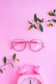 Occhiali ovali nella foto in stile estivo minimale su sfondo color rosa pastello. sveglia, fiori gialli e foglie verdi