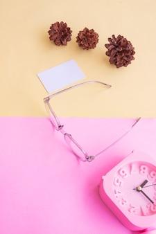 Occhiali ovali nella foto in stile estivo minimale su sfondo rosa pastello e giallo. sveglia, fiori di pino, biglietti da visita