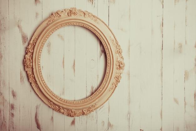 Cornice vintage ovale su fondo in legno